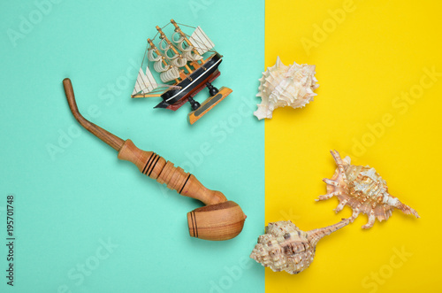 Keuken foto achterwand Schip Decorative ship, seashells, chicken pipe on a colored pastel background. Captain shipwreck. Summer Beach Concept. Top view, minimalism.