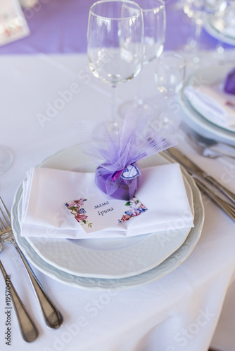 A wedding purple bonbonniere in a shape of heart lying on a white plate