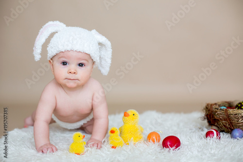 Cute little toddler baby boy, playing with colorful easter eggs and little decorative ducks