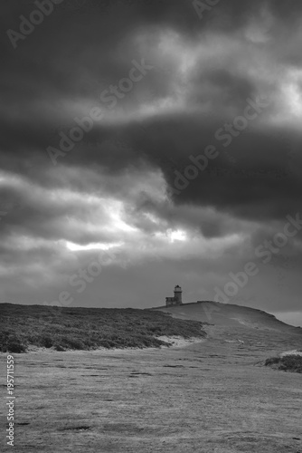 Fotobehang Grijs Stunning black and white landscape image of Belle Tout lighthouse on South Downs National Park during stormy sky