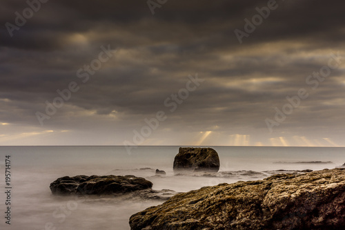 Fotobehang Strand Sunset on the beach of Fuerteventura with lava rocks, dark clouds and small waves as long exposure