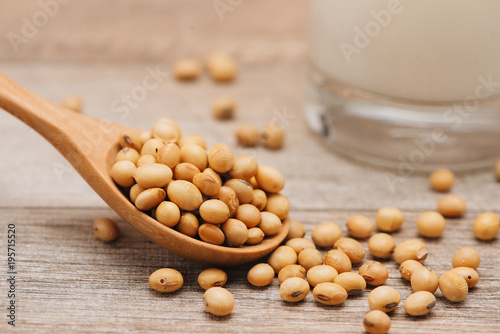 Soy beans in spoon on wooden background - 195715520