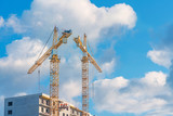 Cranes,construction crane equipment over building construction site on blue sky and clouds background - 195733563