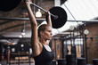 Young woman lifting weights over her head in a gym