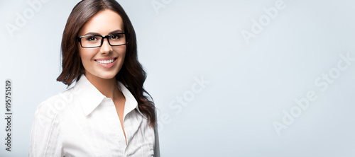 young cheerful businesswoman in glasses, over grey