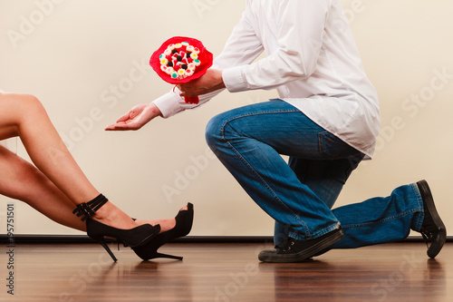 Man giving woman candy bunch flowers. Loving couple Poster
