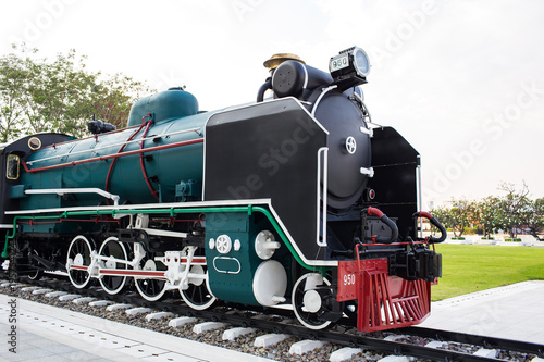 An old steam locomotive in black and green color is shown in the park for people to take a look.