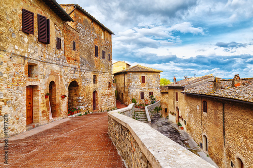 Fototapeta View of cozy paved street in San Gimignano, Tuscan medieval town, iconic landmark and popular travel destination in Italy, Europe.