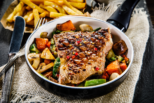 Fotobehang Steakhouse Grilled steak with french fries and vegetables served on black stone on wooden table