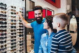 Happy family choosing sunglasses in optical store.  - 195777362