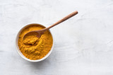 Golden turmeric powder and wooden spoon. Concrete background. Traditional indian spice. Top view.  - 195796786