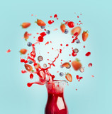Red juice or smoothie drink is poured out of glass bottle with splash and berries ingredients on turquoise background, front view. Healthy summer beverage concept - 195827717