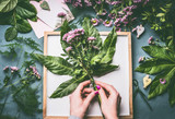 Female florist hands making flowers bunch with green leaves on work space with white tray and blank paper card, top view - 195830560