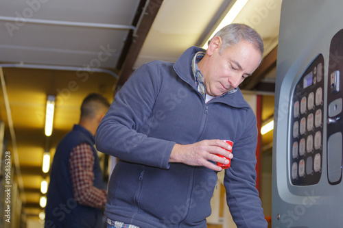 Fototapeta Man getting drink from vending machine