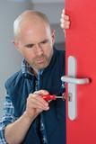 Man fixing lock on internal door - 195836318
