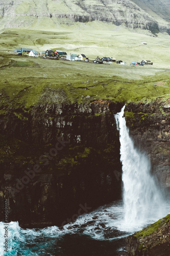Foto op Canvas Olijf Beautiful huge waterfall dropping at the ocean in Faroe islands, old village, cliffs, rainbow