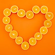 oranges cut in half are laid out in the shape of a heart on orange background