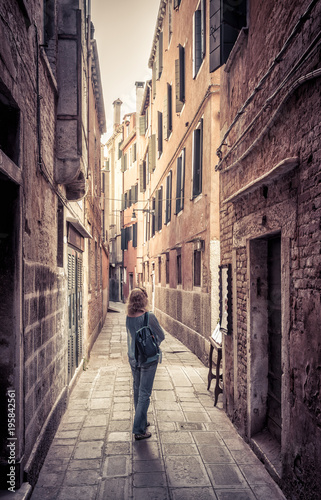 Fototapeta Girl tourist is on a narrow street in Venice, Italy