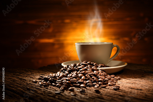Fotobehang Koffiebonen Cup of coffee with smoke and coffee beans on old wooden background