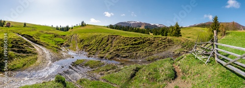 Fotobehang Honing panorama of mountainous rural countryside. spruce forest on grassy slopes. wooden fence near the brook. mountain ridge with snowy tops in the distance