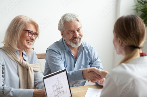 Leinwandbild Motiv Smiling satisfied senior couple making sale purchase deal concluding contract handshaking real estate agent or realtor, happy older family and broker shake hands agreeing to buy new house at meeting