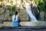 Woman sitting near waterfall in Dalat, Vietnam
