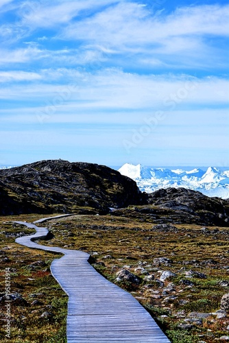 Keuken foto achterwand Blauwe hemel hiking on boardwalk in Ilulissat Greenland - beautiful icebergs in the Disko Bay / Baffin Bay - nature, rocks, blue sky, ice sea