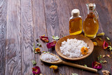 SPA concept: composition of spa treatment with natural sea salt, aromatic oil and flowers on wooden background - 195881731