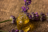 Bottle of lavender oil and bunch of lavender flowers  - 195885713