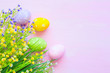 Easter eggs in pastel color with flowers on wooden pale pink background. Top view