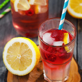 Glass of water with raspberries, slices of lemon and ice