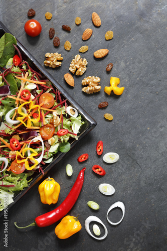 Salad ingredients with lettuce, cabbage, nuts and seeds and red  and yellow hot pepperson slate from above - 195895538