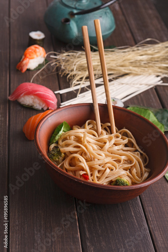 Bowl of rice noodles with soy souce on wooden background
