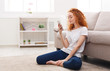 Young redhead girl with smartphone sitting on the floor