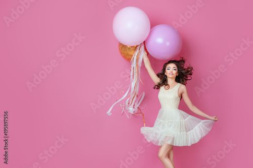 Cheerful Beautiful young girl in dress with sparkle and pink helium balloons enjoying birthday photoshoot dancing and smiling on pink background Cute woman posing in studio. Fashion Lifestyle Emotions - 195897556