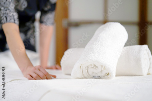 Foto op Canvas Spa The girl folds a towel, prepares a workplace in the spa for the reception of clients. The maid is preparing a room for the spa salon. Woman masseuse in the workplace. The concept of health and beauty.