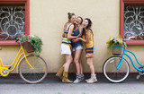 Happy boho chic girls pose with bicycles near house facade - 195907375