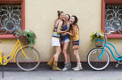 Happy boho chic girls pose with bicycles near house facade