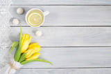 Yellow tulips, lemon tea and candies on white wooden table