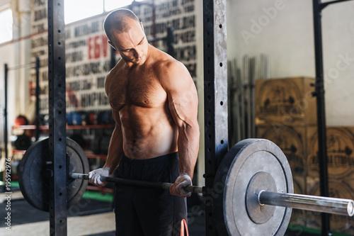 Boczny widok patrzeje jego mięśnie męska atleta podczas gdy podnoszący barbell w gym