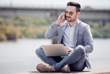 Young attractive man sitting outdoors and using phone - 195915186
