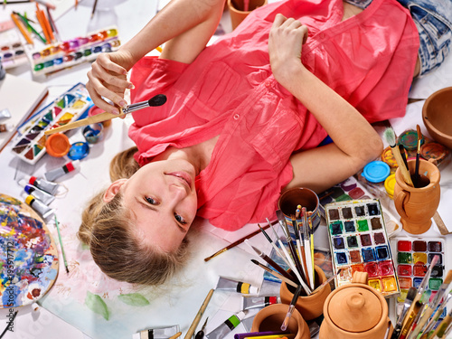 Authentic artist children girl paints with set palette watercolor paints palette and brush in morning sunlight. Top view indoor home interior handmade crafts. Photoshoot for artist.