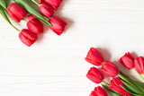 Bouquet of red tulips on white wooden background. Flat lay. Copy space.