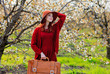 girl with suitcase in blossom cherry garden