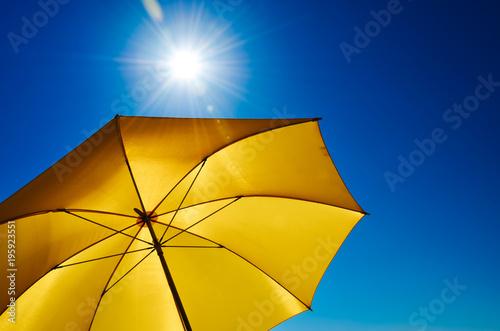 Leinwanddruck Bild Gelber Sonnenschirm mit strahlend heller Sonne und blauem Himmel