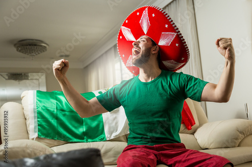 Mexican fan watching a soccer match at home