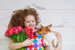 Laughing girl hugging a puppy and holding red tulips.