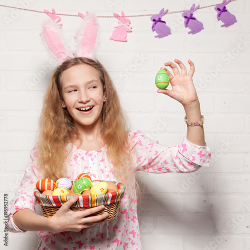 Child is holding a basket with Easter eggs
