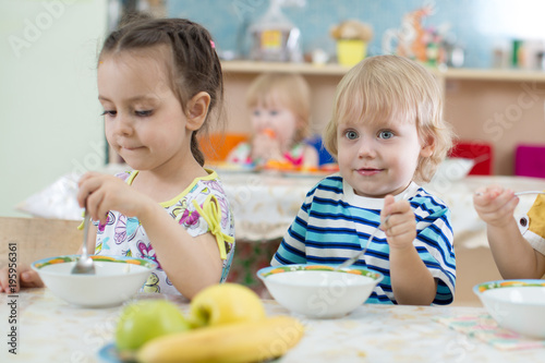 Kids have lunch in kindergarten or day care centre