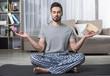 Portrait of calm bearded male sitting on yoga carpet in living room